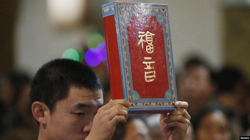 北京市一家天主教堂在进行圣诞弥撒期间,一名神职人员手举圣经。