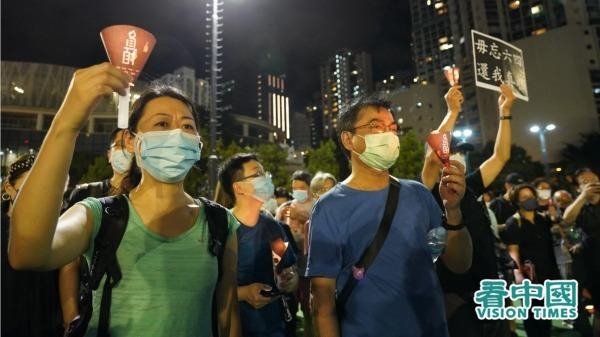 市民燃點起燭光,悼念八九六四死難者,也有人舉起「毋忘六四、還我真相」紙牌。(圖片來源:Adrian/看中國)