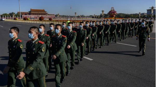 中国士兵戴着防护口罩从天安门广场走过