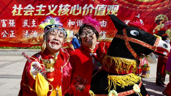 """2021年4月28日,北京一处公园里,人们在巨幅""""社会主义核心价值观""""的标语前舞秧歌。(图片来源:Fred LeeGetty Images)"""